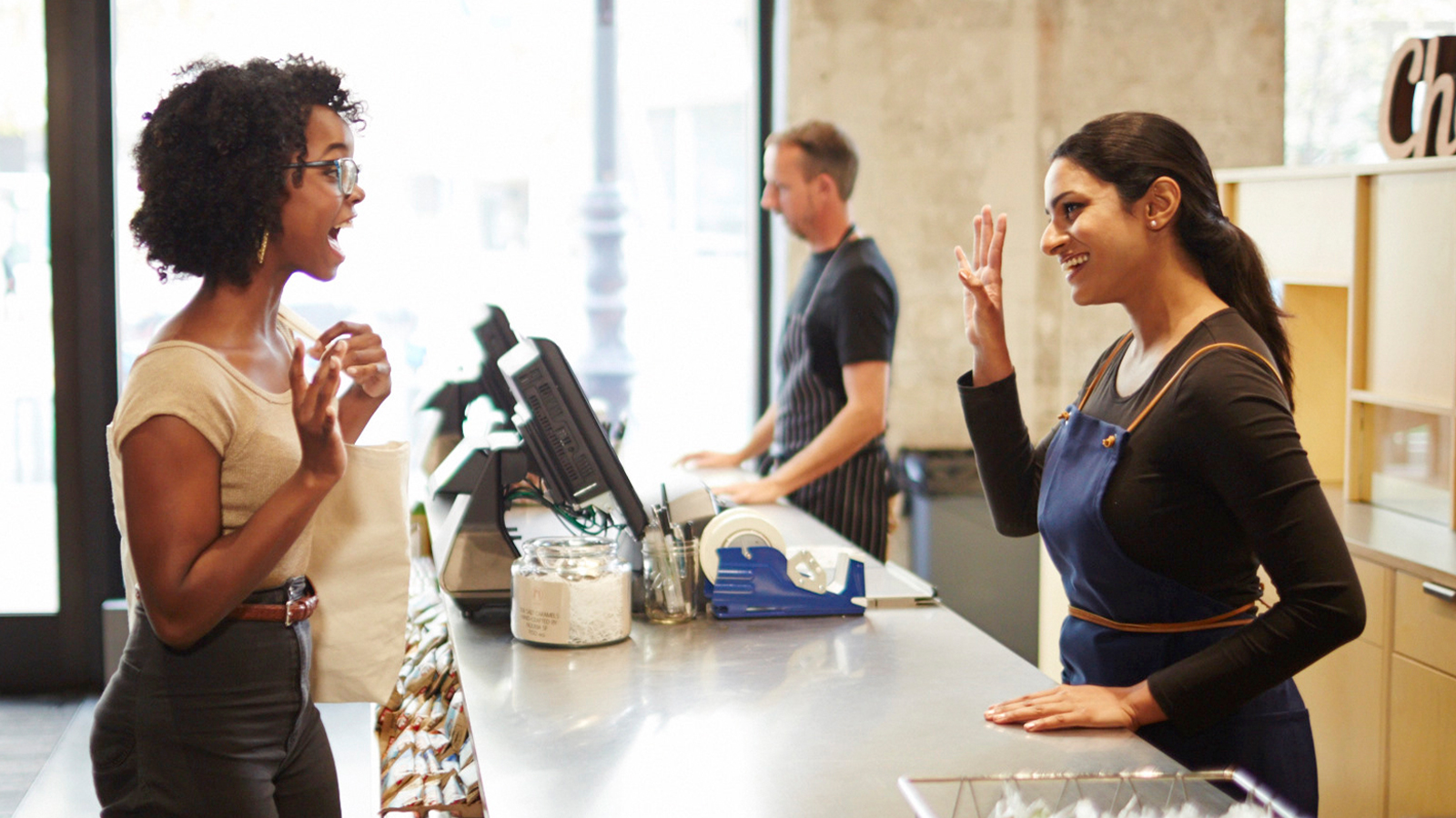 Woman greeting retail store clerk at counter.