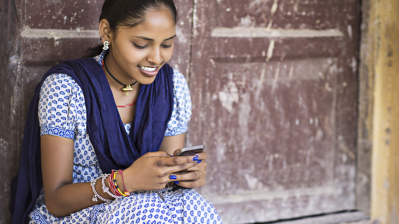 Indian woman smiling while using her mobile phone.