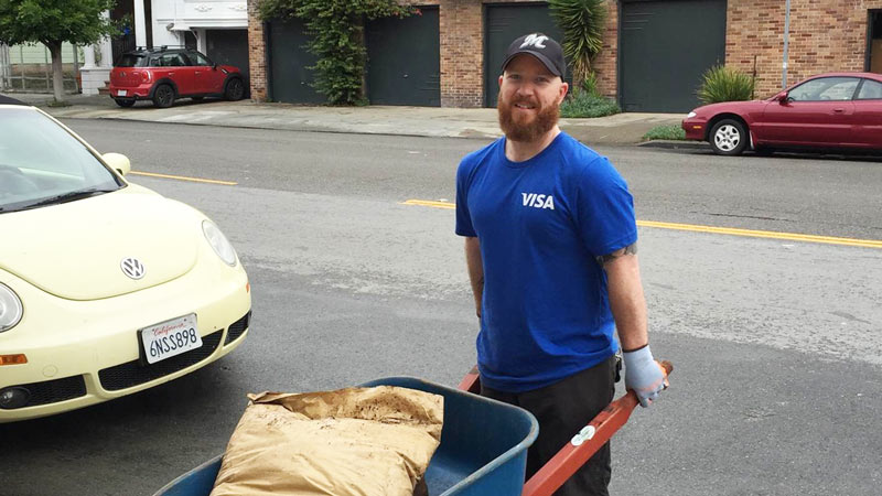 Visa volunteer using wheelbarrow full of landscaping supplies in urban environment.