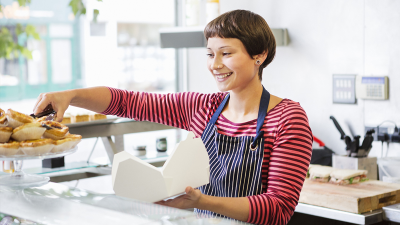 bakery owner serving a customer and smiling