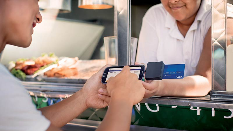 Customer completing a transaction using a mobile credit card reader at a food truck.
